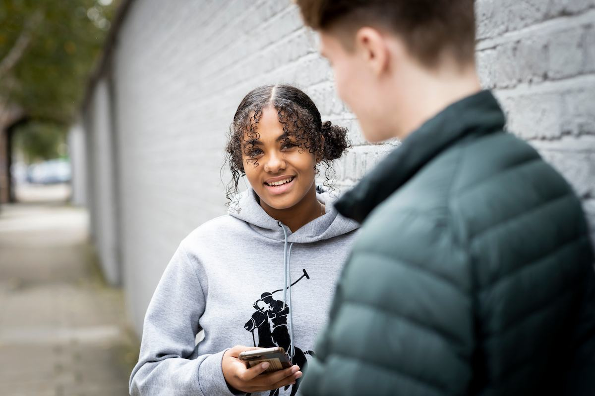 A young person is talking to a friend whilst holding their phone