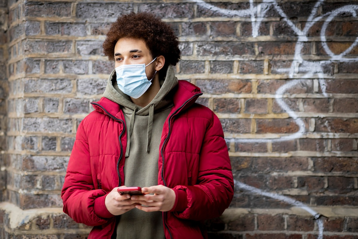 A young man is standing in front of a brick wall. He is wearing a mask. He is living with smokers. This is a wide-angle image.