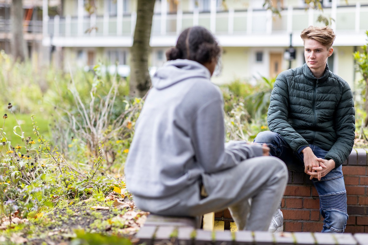 A young man is talking to his friend. He wants to help her quit smoking. This is a wide-angle image.