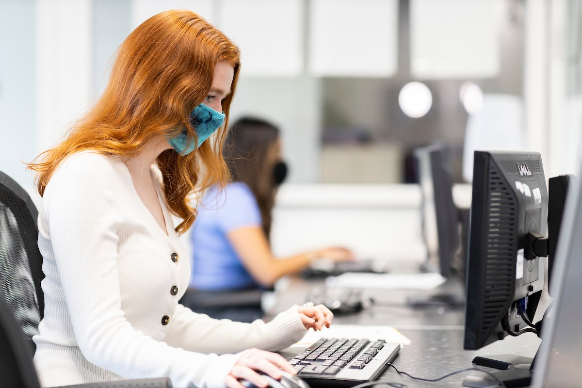 A young, red-headed woman is sitting at a desk. She is researching 'What is a legal high?' This is a wide-angle image.
