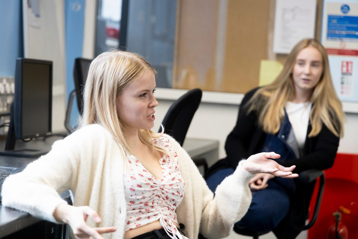 Two young people are talking in a classroom