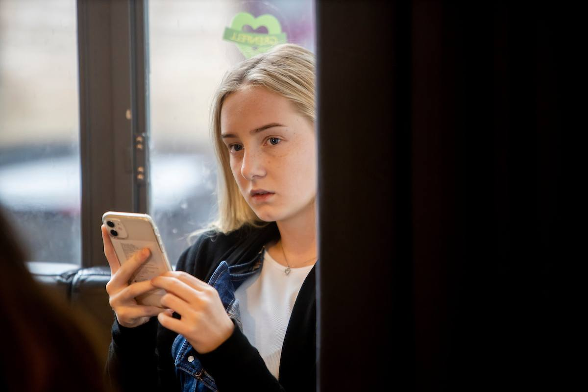 A young, blonde woman is holding her phone. She is looking up cocaine nose. This is a wide-angle image.