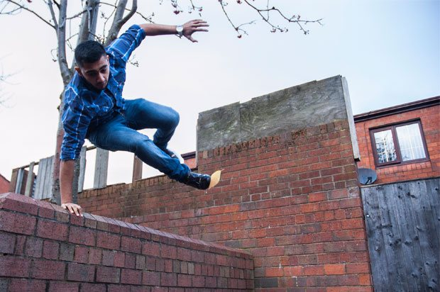 Boy jumping over a wall