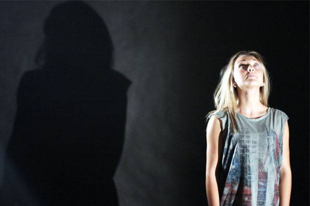 Girl looking up, standing against black backround with her shadow behind her