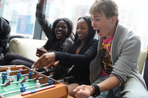 3 young people winning at table football