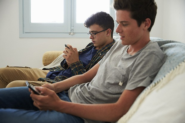 two young men sat together on their phones.