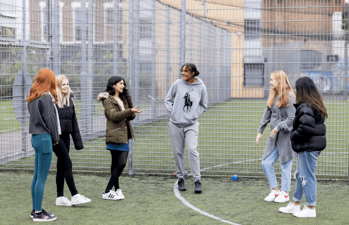 A group of young people are standing on a field. They are in a semi-circle. They are discussing mixing drugs. This is a wide-angle image.