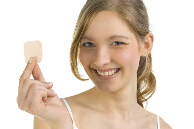 Yound woman holding a contraceptive patch