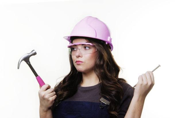 Girl with a pink hard hat and hammer