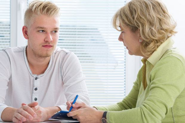 Young man sat talking to therapist or doctor