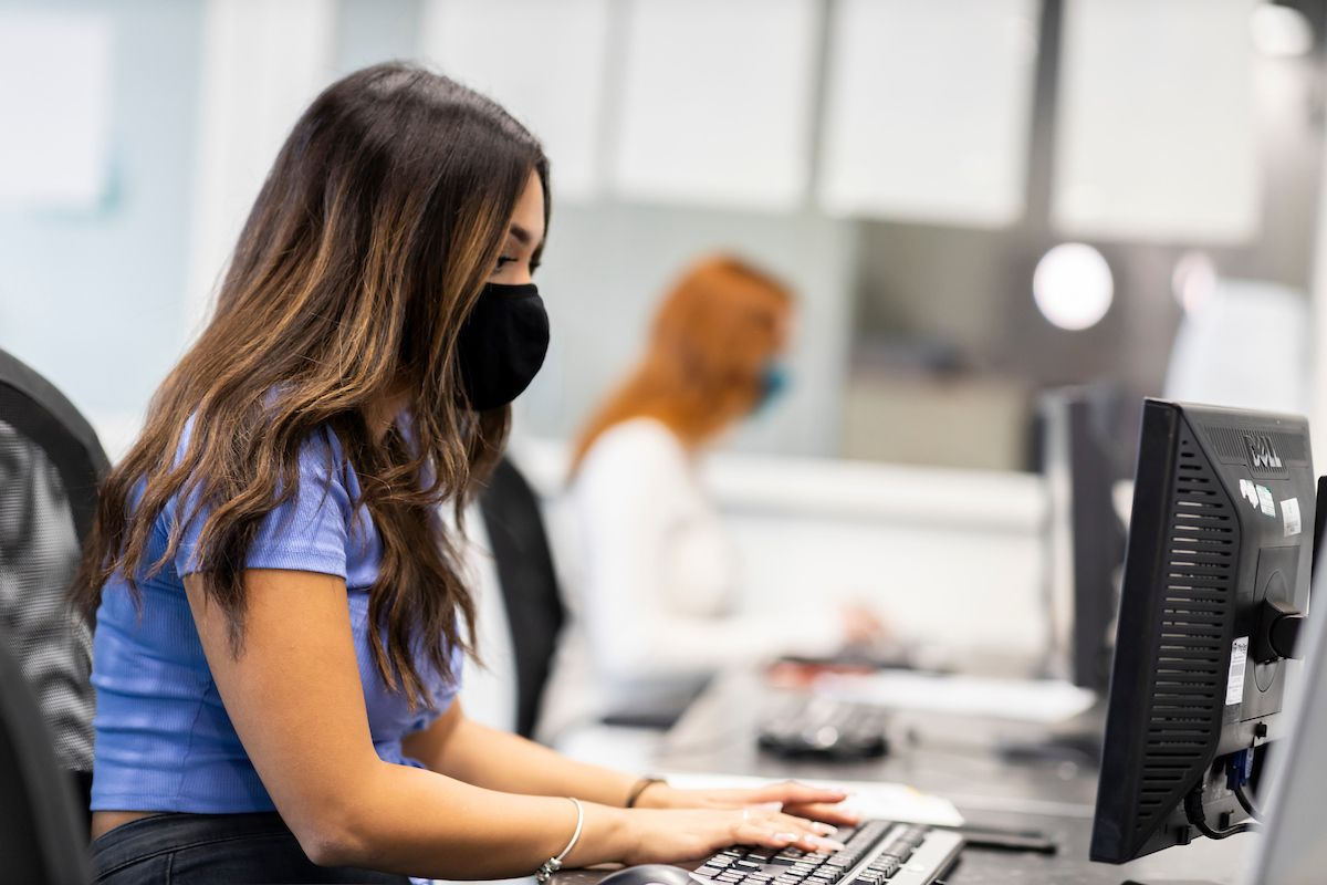 A young woman is sitting at a desk. She is wearing a mask. She is looking up flying agaric mushrooms. This is a wide-angle image.