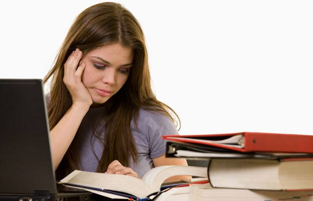 Girl studying with books and laptop