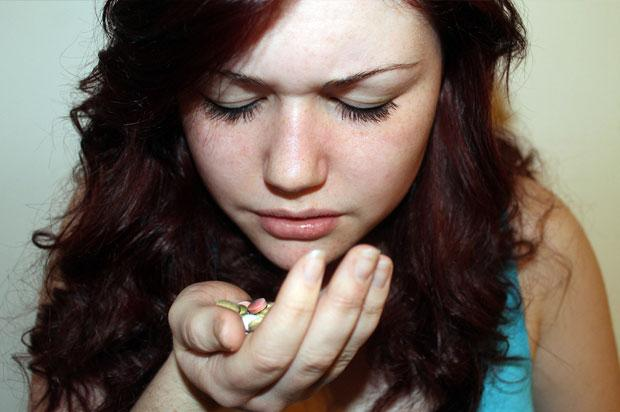 Girl holding pills in her hand