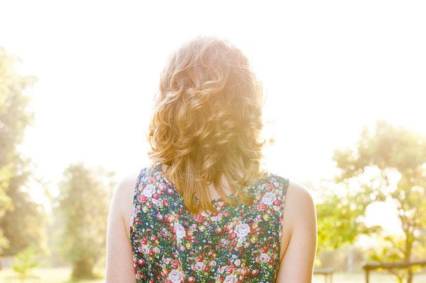 Back of girl's head as she stands in a garden in sunshine