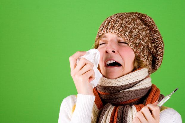 Girl in a hat and scarf sneezing into a tissue