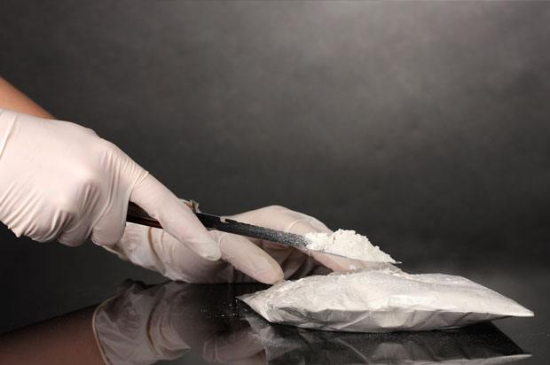Hands with gloves using a knife to open a packet of cocaine