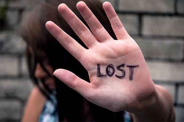 Girl holding hand up at camera, with word 'LOST' written across the palm