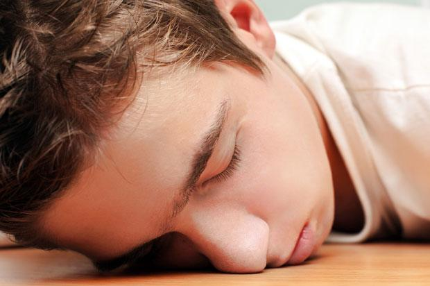 Boy passed out on laminate flooring