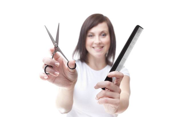 Girl holding scissors and comb for hairdressing