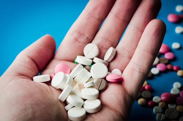 Hand holding lots of different pills