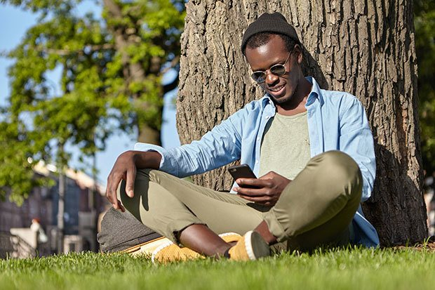 Young man sat in the sun on his phone. He is smiling lightly.