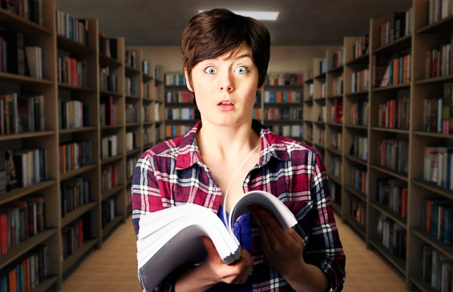 Girl with a huge book looking confused.