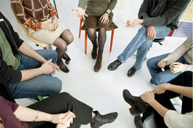 People sitting on chairs in a circle at group therapy