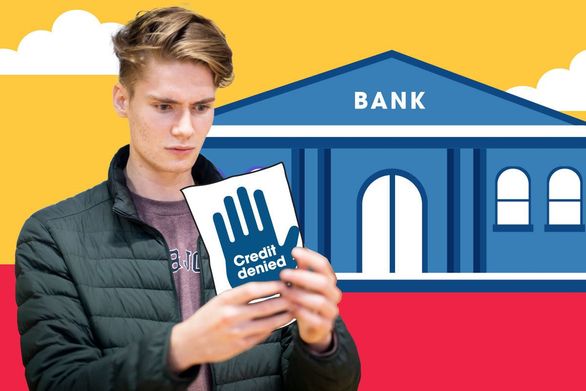 """A young person stands outside a bank holding a card with a raised hand on it which says """"credit denied"""""""