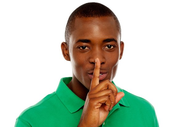 Young man holding his index finger to his lips