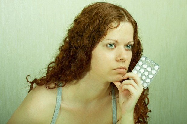 Girl looking sad with pills
