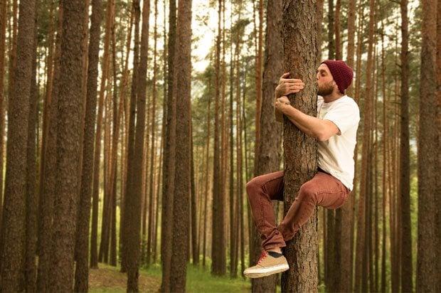 Man hugging a tree so feet of the floor