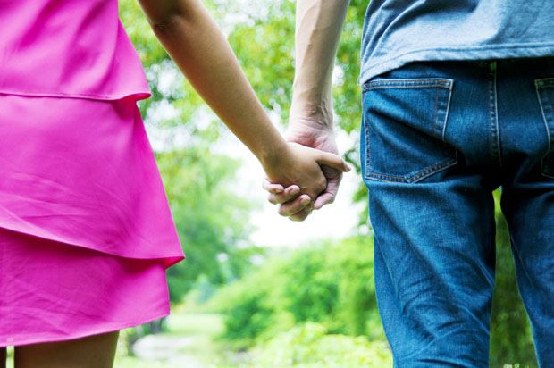Couple walks through wooded area holding hands.