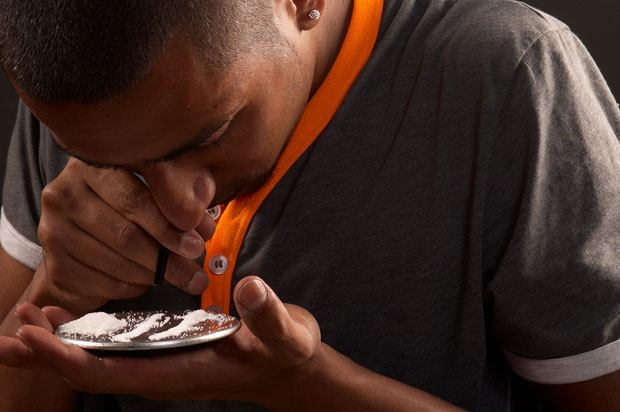 Young man snorting white powder