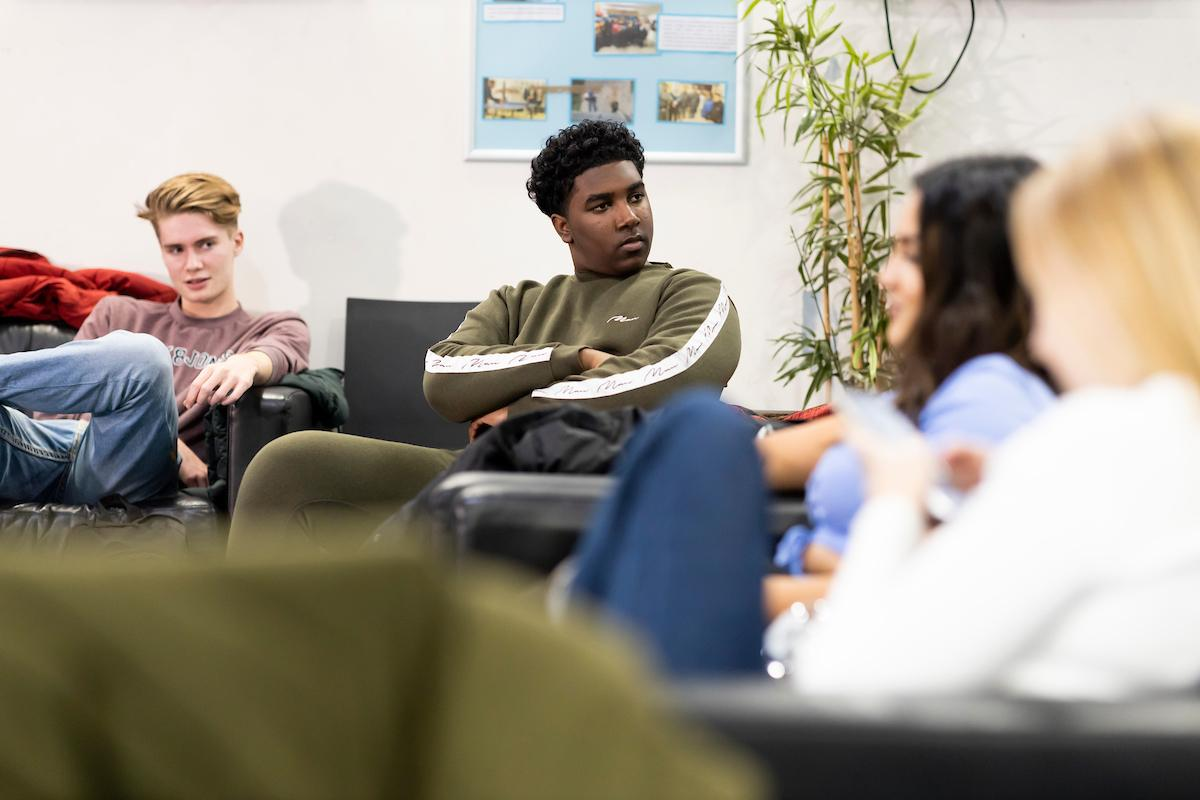 A group of young people are sitting on a sofa. They are discussing Amsterdam drug laws. This is a wide-angle image.