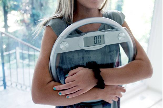 Girl holding electronic weighing scales