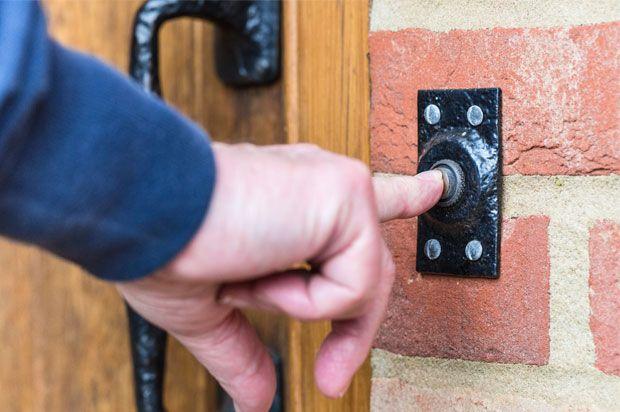 Hand ringing a doorbell