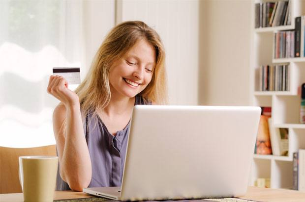 Girl smiling looking at her laptop holding a debit card