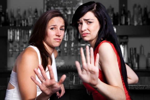 Two upset looking girls holding their hands up to someone.