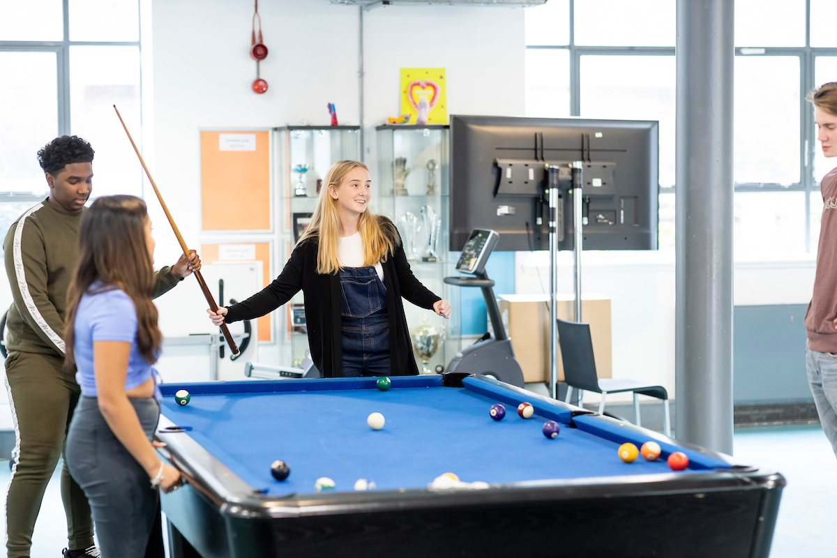A group of young people are standing around a pool table. They are planning a cocktail party. They look happy. This is a full-body image.