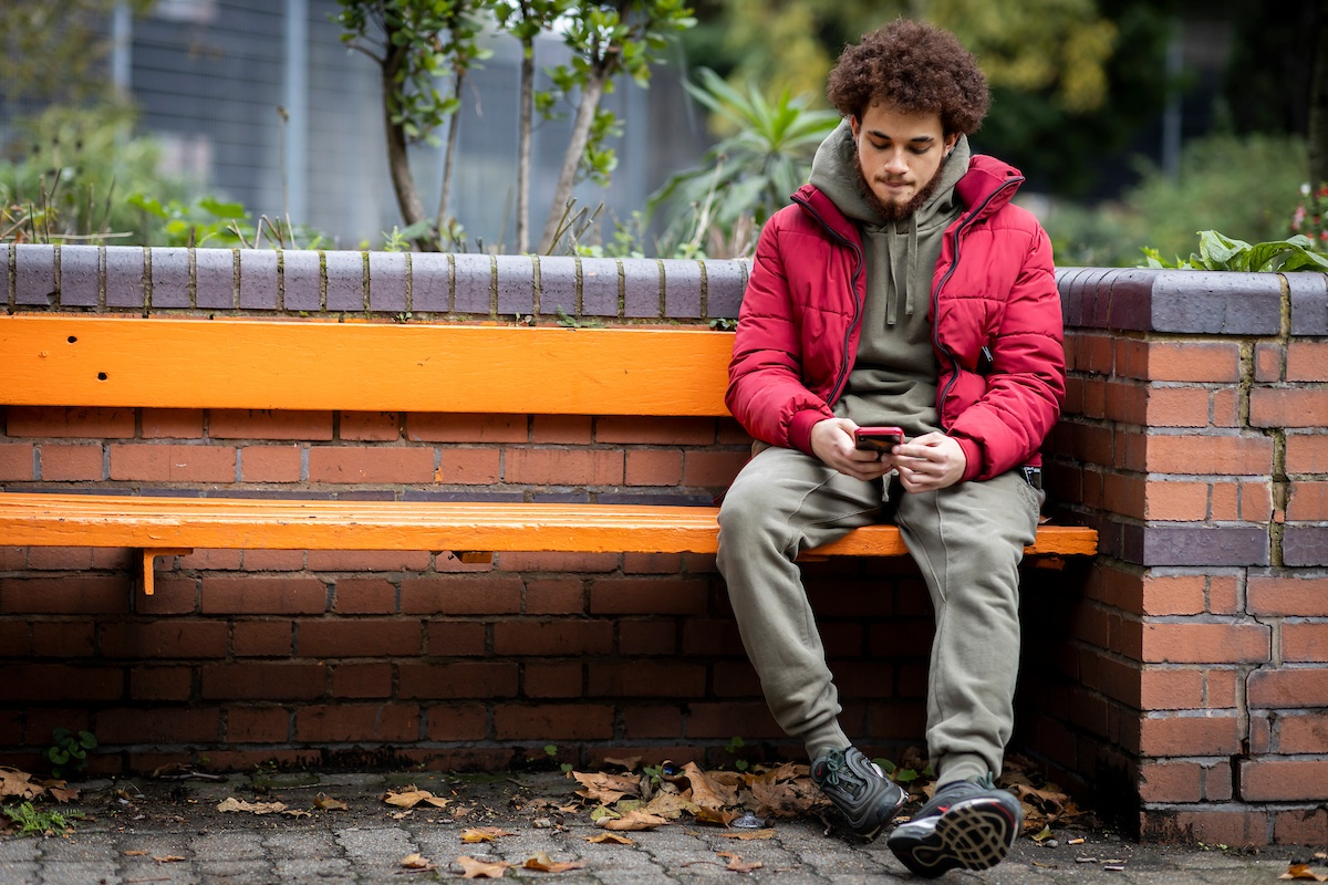 A young man is sitting on a bench alone. He is looking up how to stop taking drugs. He is wearing a red puffer jacket and khaki sweatset. He looks concerned. This is a full-body image.