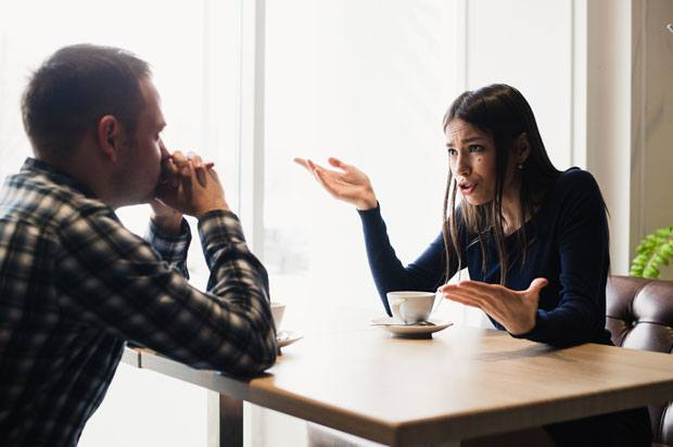 Man and woman sit at table and have argument