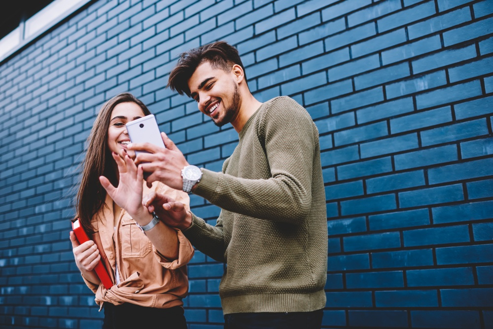 Two young people are standing in front of a brick wall. They are looking up how to confront someone. This is a wide-angle image.