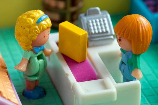 polly pockets standing at a checkout till.