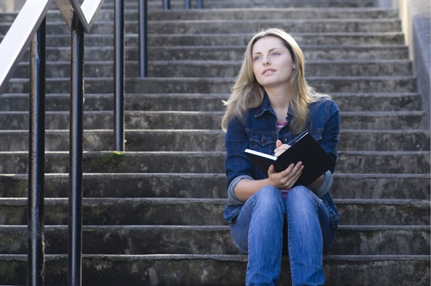 Girl sat on the stairs, writing her diary