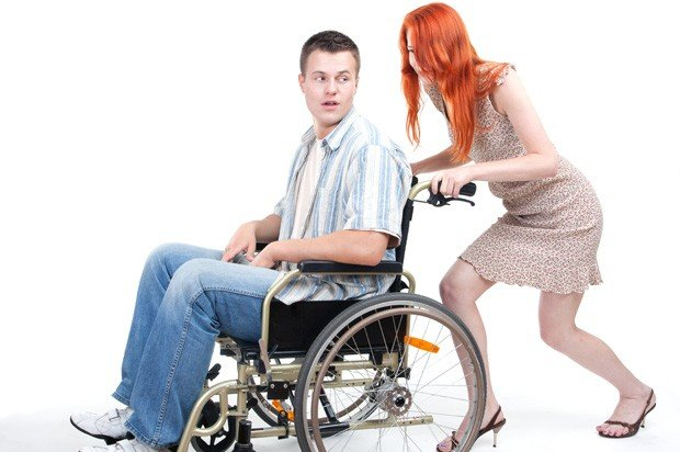 Young woman pushing a young man in a wheelchair