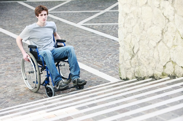 A young man in a wheelchair unable to get up the stairs