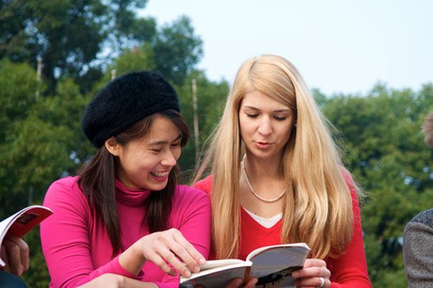 two female students looking at a book