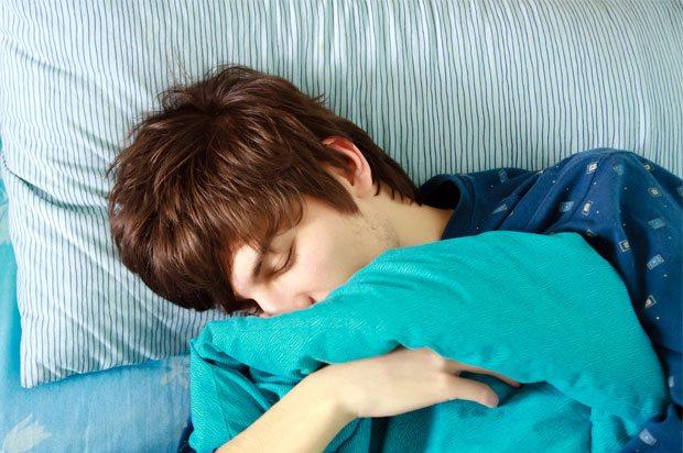 Boy asleep hugging his duvet