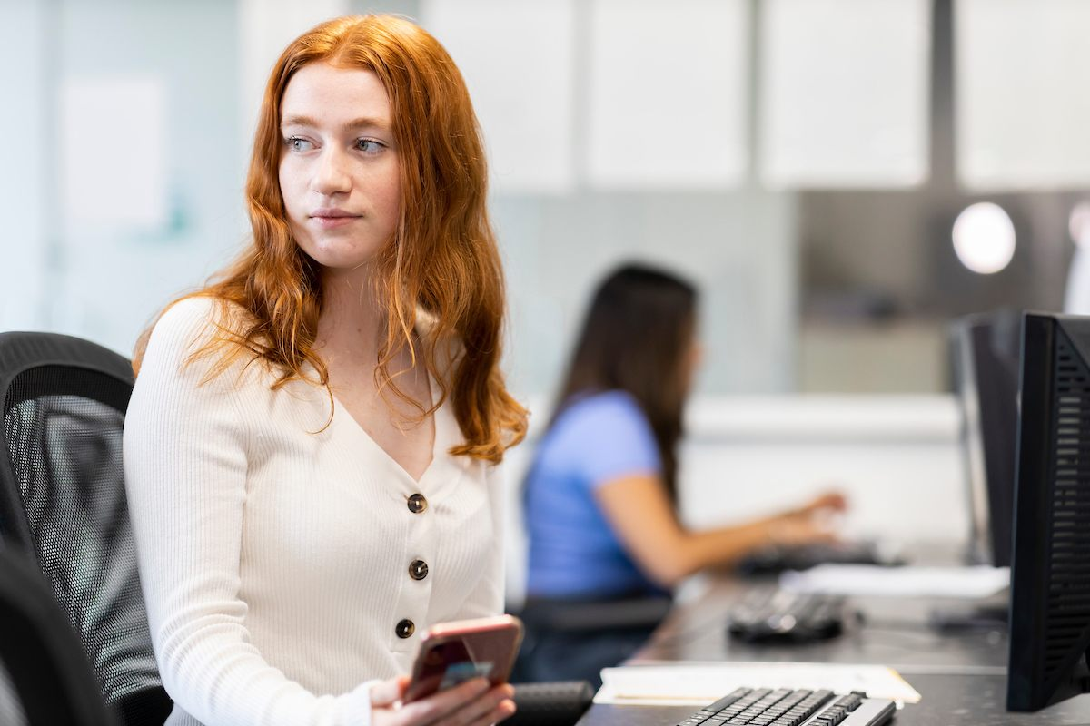 A red-headed woman is sitting at a desk. She has her phone in her hand. She is thinking about the benefits of not drinking alcohol. She is looking off to the distance, pensively. This is a close-up image.