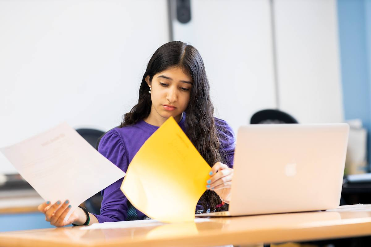 A young woman is sitting at a desk. She is going through papers on dxm. This is a wide-angle image.
